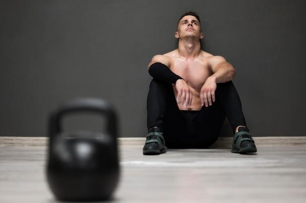 Homem de ângulo baixo cansado de treino