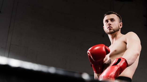 Homem de ângulo baixo, treinamento para ser um boxeador com espaço de cópia