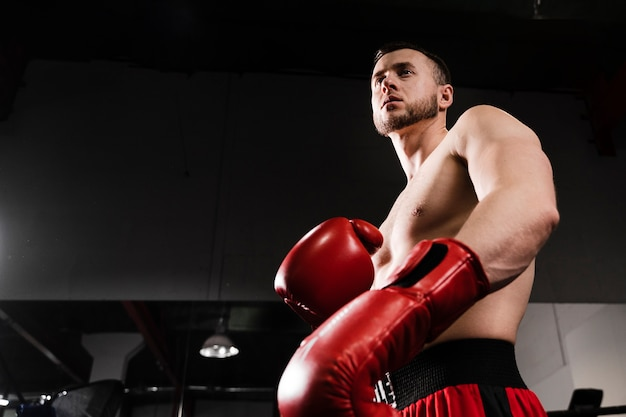 Homem de ângulo baixo, treinando como boxeador
