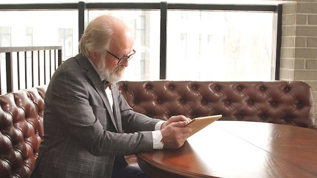 Homem de anos maduros de terno clássico e óculos trabalha em um tablet em seu escritório