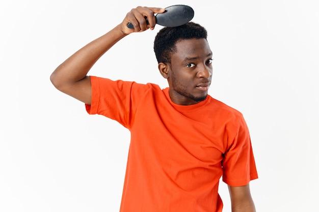 Homem de aparência africana com uma camiseta laranja e um pente nas mãos