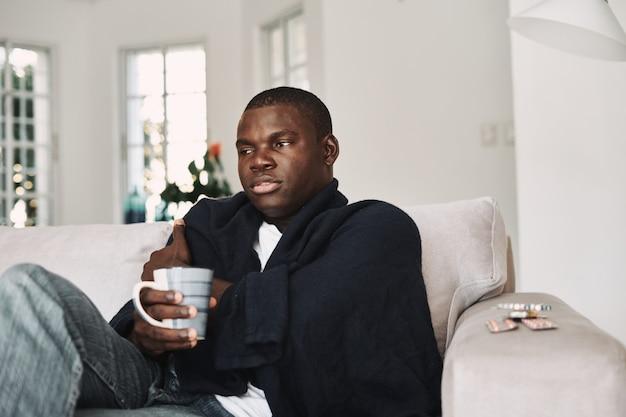 Homem de aparência africana sentado no sofá em casa, remédio para problemas de saúde