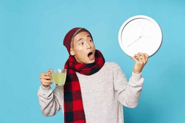 Homem de aparência asiática com um relógio nas mãos, um tratamento de bebida quente
