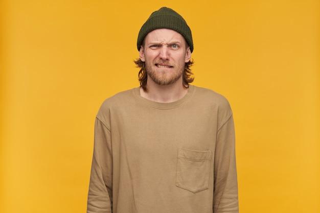 Homem de aparência brava, cara barbudo carrancudo com penteado loiro. usando gorro verde e suéter bege. morde o lábio. isolado sobre a parede amarela