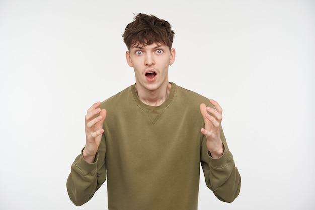 Homem de aparência chocada, cara bonito com cabelo castanho, piercing e cerdas usando um suéter de cor cáqui. momento tenso. conceito emocional. isolado sobre a parede branca