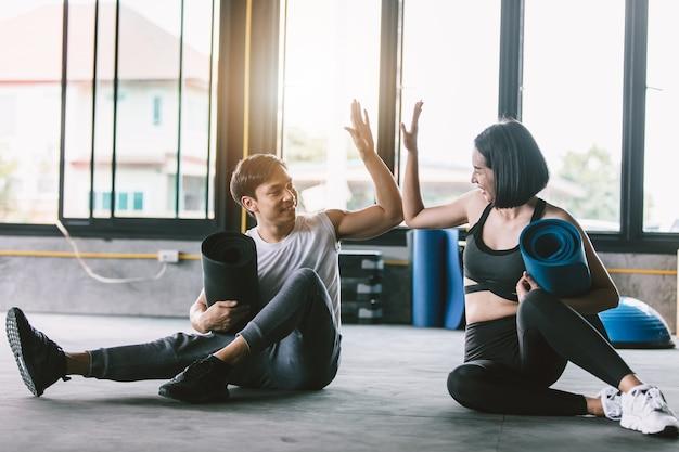 Homem de aptidão asiática e mulher dando uns aos outros mais cinco após a sessão de treinamento em gy