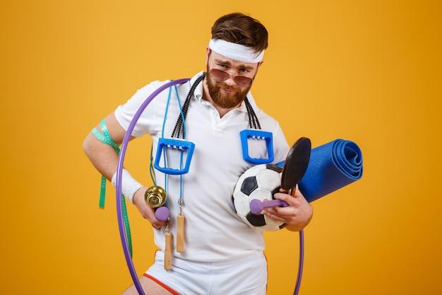 Homem de aptidão barbudo satisfeito em óculos de sol segurando equipamentos esportivos
