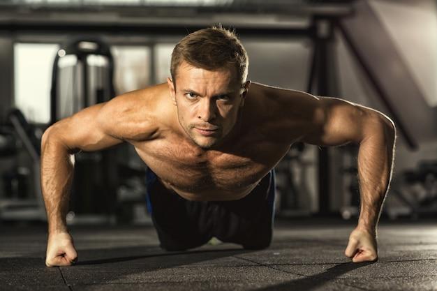 Homem de aptidão com confiança fazendo flexões na academia