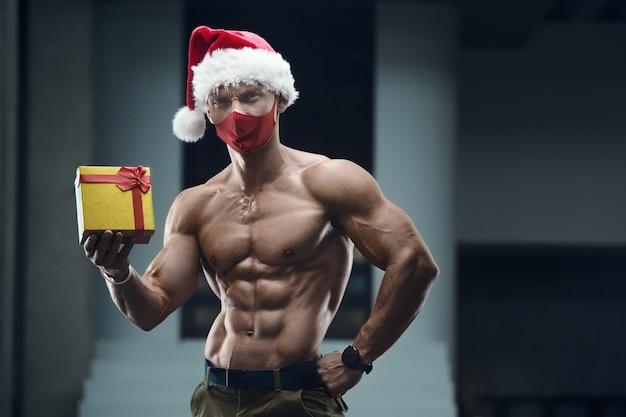 Homem de aptidão com fantasia de chapéu de papai noel no ginásio com uma caixa de presente.