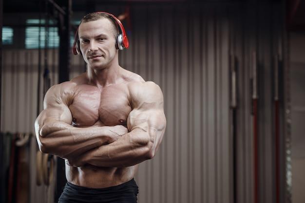 Homem de aptidão com fones de ouvido em treino no ginásio