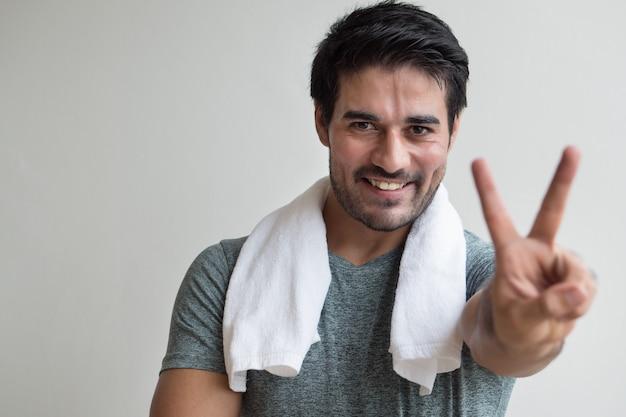 Homem de aptidão confiante apontando dois dedos; retrato de homem asiático de aptidão feliz, saudável e confiante apontando o sinal de dedos número dois, v para gesto de vitória com a mão; modelo homem adulto asiático do norte da índia
