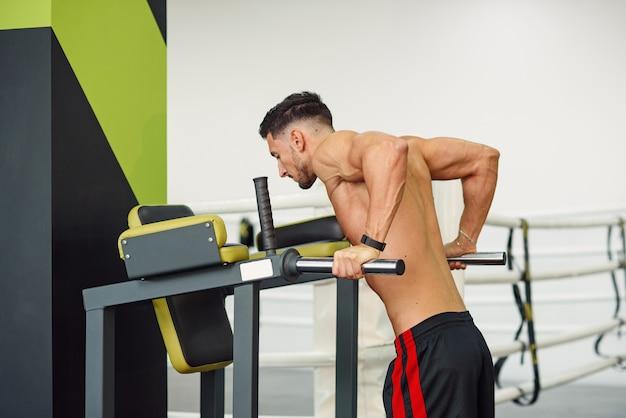 Homem de aptidão desportiva fazendo flexões em barras paralelas enquanto treinava no ginásio moderno. conceito saudável e esportivo.