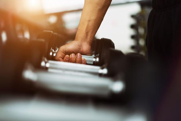Homem de aptidão em treinamento mostrando exercícios com halteres no ginásio