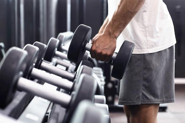 Homem de aptidão em treinamento, mostrando exercícios com halteres no ginásio.