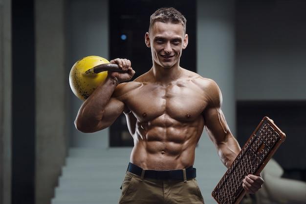 Homem de aptidão em treino no ginásio bombeando os músculos com kettlebell.