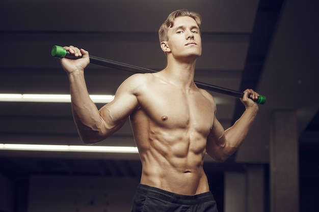 Homem de aptidão em treino no ginásio com músculos alongamento da barra corporal. conceito de fitness e musculação. fisiculturista caucasiana fazendo exercícios abdominais na academia