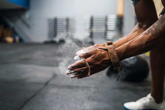 Homem de aptidão esfregando as mãos com pó de magnésio giz.