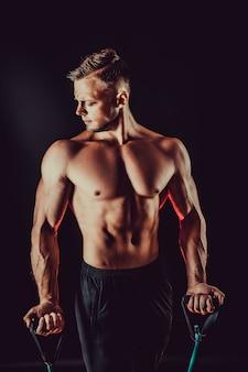 Homem de aptidão exercitando com faixa de alongamento no estúdio.