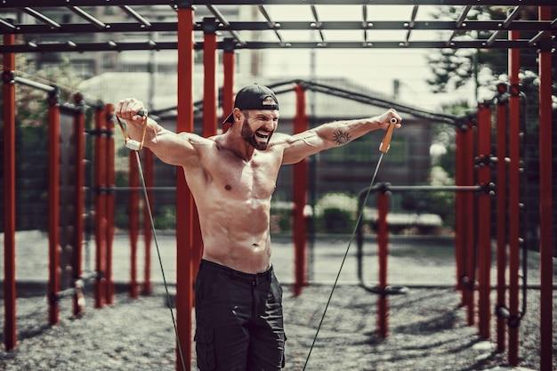 Homem de aptidão exercitando com faixa de alongamento no ginásio ao ar livre.