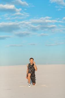 Homem de aptidão fazendo exercícios no deserto de areia. esporte