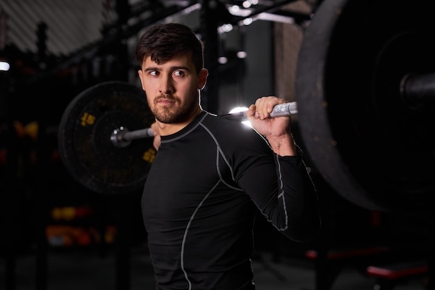 Homem de aptidão fazendo um treinamento de peso, levantando a barra. jovem atleta treinando sozinho. fisiculturista levantando peso. instrutor cruzado apto no ginásio. conceito de esporte