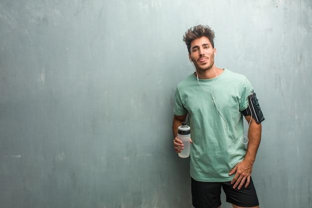 Homem de aptidão jovem contra uma expressão de parede grunge de confiança e emoção, diversão e amigável