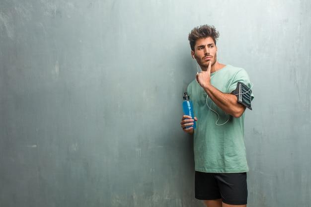 Homem de aptidão jovem contra uma parede de grunge, pensando e olhando para cima