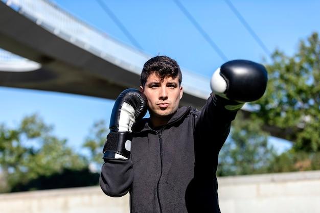 Homem de aptidão jovem esportes ao ar livre no parque fazer exercícios de boxe.