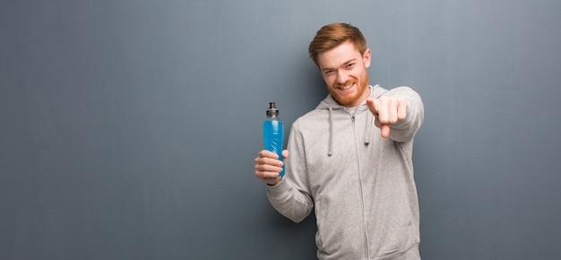 Homem de aptidão jovem ruiva alegre e sorridente, apontando para a frente. ele está segurando uma bebida energética.