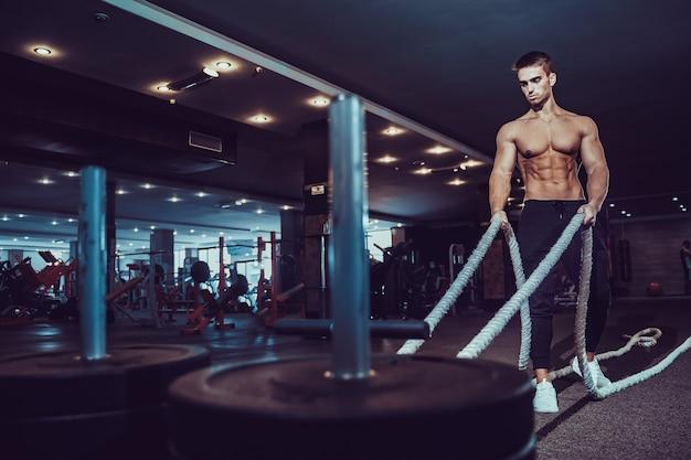 Homem de aptidão malhando com cordas de batalha no ginásio.