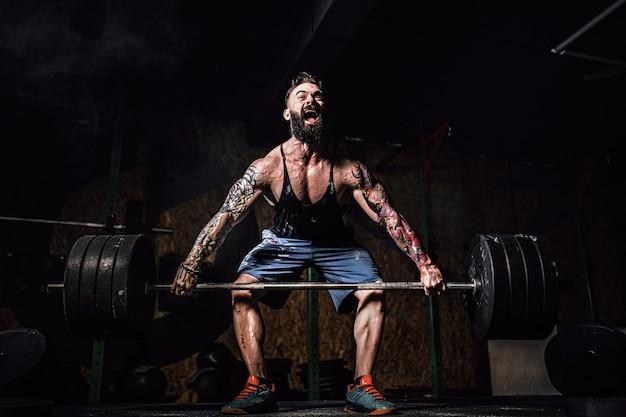 Homem de aptidão muscular fazendo levantamento terra de um barbell no moderno centro de fitness. treino funcional.