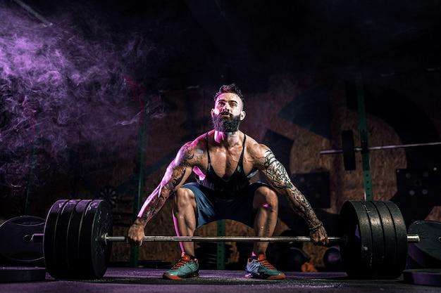 Homem de aptidão muscular fazendo levantamento terra de uma barra no moderno centro de fitness na fumaça. treino funcional. snatch exercício