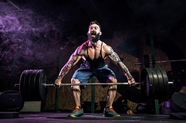 Homem de aptidão muscular fazendo levantamento terra de uma barra no moderno centro de fitness na fumaça. treino funcional. snatch exercício Foto Premium