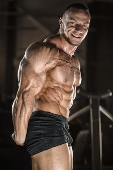 Homem de aptidão muscular fisiculturista fazendo exercícios de braços no ginásio