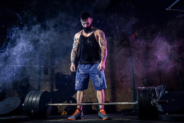 Homem de aptidão muscular, preparando-se para levantamento terra de um barbell no moderno centro de fitness. treino funcional.