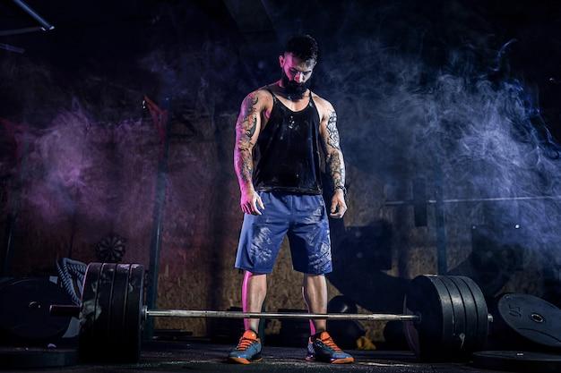 Homem de aptidão muscular se preparando para levantar uma barra no moderno centro de fitness. treino funcional. snatch exercício