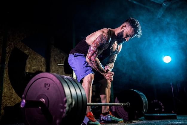 Homem de aptidão muscular se preparando para levantar uma barra no moderno centro de fitness.