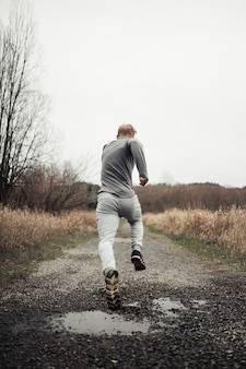Homem de aptidão saudável correndo na trilha da floresta