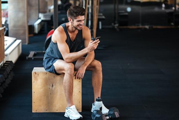 Homem de aptidão se senta na caixa com o telefone. sorridente