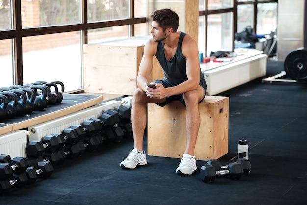 Homem de aptidão se senta na caixa no ginásio. e olhando para longe