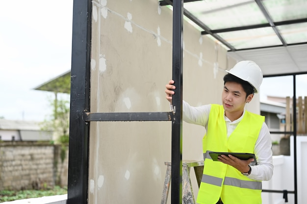 Homem de arquitetura verificando o prédio com um tablet