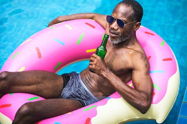 Homem de ascendência africana flutuando na piscina por inflável