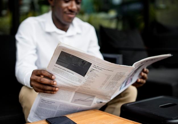 Homem de ascendência africana sentado lendo um jornal ao ar livre