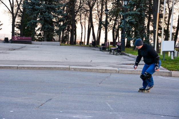 Homem de atividade de lazer patinação no centro da cidade, no pôr do sol. inverno. patinação de rua.