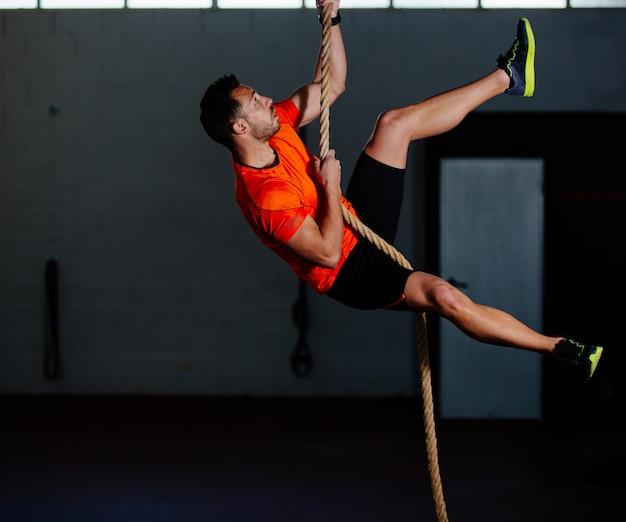 Homem de atleta crossfit subindo uma corda no ginásio