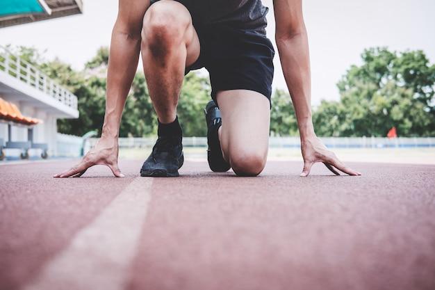 Homem de atleta de aptidão se preparando para correr na pista de estrada, conceito de bem-estar de treino de exercício