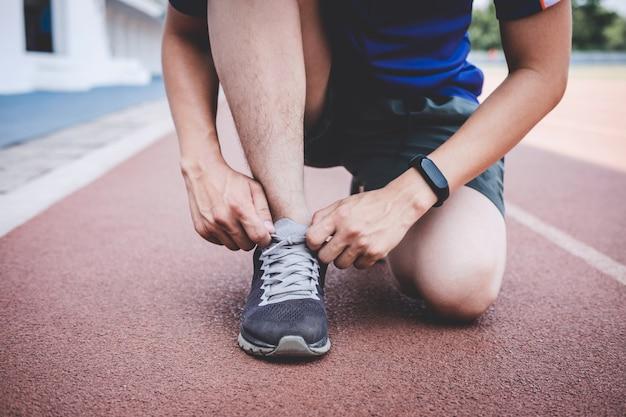 Homem de atleta jovem aptidão correndo na pista de estrada, bem-estar de treino exercício e corredor amarrar cadarços antes de executar