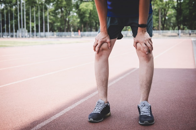 Homem de atleta jovem fitness descansar durante e cansado na pista de estrada, exercício bem-estar de treino