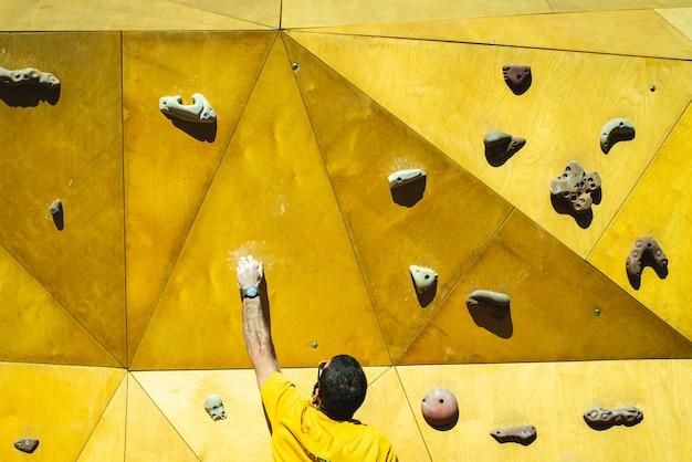 Homem de atleta tentando alcançar o topo de uma parede de escalada com a força de suas mãos e pernas.