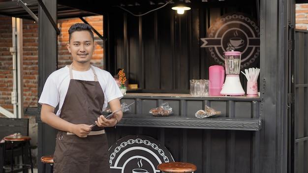 Homem de avental de bar asiático preparando lista de menu no tema de container angkringan